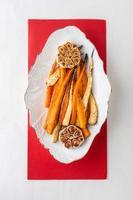 gebackene junge Karotten mit Knoblauchscheiben auf weißem Teller zubereitet foto