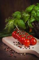 Arrangement aus Zweig Tomaten und frischen Kräutern foto