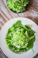 Salat mit Spinat, Gurke und Microgreens auf Holzhintergrund foto