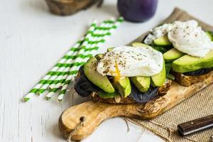 gesundes Sandwich mit Avocado und pochierten Eiern foto