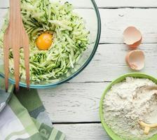 Hintergrund mit Zutaten zum Kochen von Zucchinipfannkuchen foto