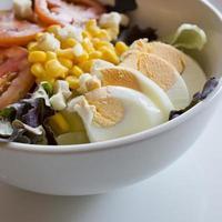 Salat mit Eiern mit Hühneraugen und Tomaten