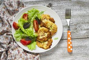 Zucchinipfannkuchen und frischer Gemüsesalat auf weißem Teller foto