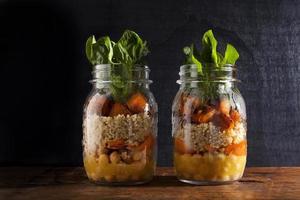 Einmachgläser mit heißem Salat: Kichererbsen, Arrots, Quinoa, geröstete Pu foto