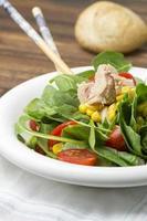 frischer Spinatsalat mit Thunfisch und Mais, Kirschtomaten foto