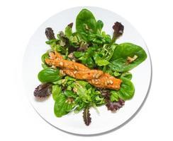 Salat aus buntem frischem Blattspinat mit geräuchertem Lachs, isoliert foto