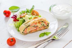 Strudeltorte mit Lachs und Spinat, serviert auf weißem Teller foto