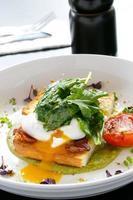 pochierte Eier, Vollkornbrot, Tomaten und Gemüse foto