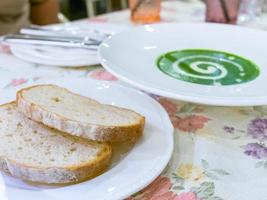 Spinatcremesuppe und zwei Brote foto