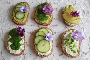 grüne Sauerteig-Sandwiches mit offenem Gesicht und lila essbaren Blüten foto