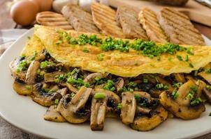 rustikales Omelett mit Pilzen auf Schnittlauch foto