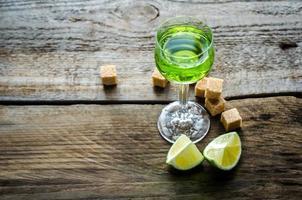 Glas Absinth mit Limetten- und Zuckerwürfeln foto