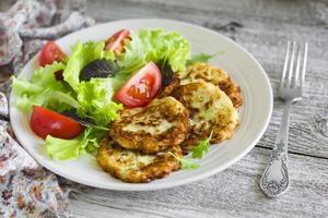 Zucchinipfannkuchen und frischer Gemüsesalat in weißer Platte foto