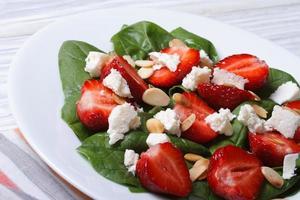 frischer Salat aus Erdbeeren, Spinat, Ziegenkäse und Mandeln foto
