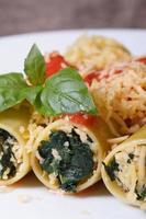 italienische Cannelloni mit Spinat, Käse und Tomatensauce foto