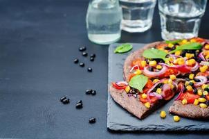 schwarze Bohnenkruste Pizza mit Mais, Spinat, Tomaten, schwarzen Bohnen foto