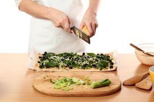 Pizza mit Lauch und Spinat machen. Serie.
