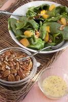 Spinatsalat mit Pekannüssen, Pfirsichen und Dressing foto