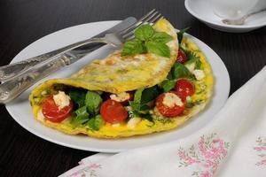 Omelett mit Spinat, Basilikum, Kirschtomaten und Käse adyg foto