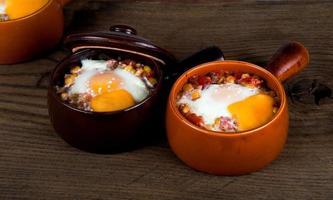 Eier mit cremiger Sauce, Mais, Schinken, Käse und Kräutern gebacken foto