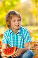 Porträt des Jungen, der Wassermelone auf Blättern hält