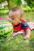 kleiner Junge beißt Wassermelone foto