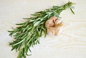 ganzer Bio-Knoblauch und frisches Rosmarinkraut auf Holztisch foto
