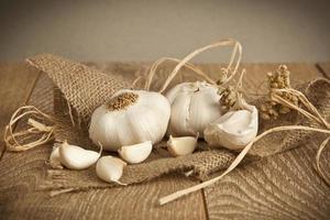 Bio-Knoblauch ganz und Nelken auf dem hölzernen Hintergrund foto