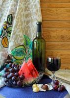 Stillleben mit Wein, Obst und Pralinen.