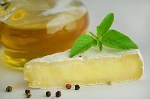 Käse mit Gewürzen auf weißem Hintergrund foto