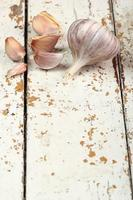 Knoblauchknollen und Nelken auf schälendem Farbplankentisch foto