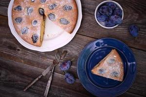 hausgemachter Pflaumenkuchen auf hölzernem Hintergrund foto