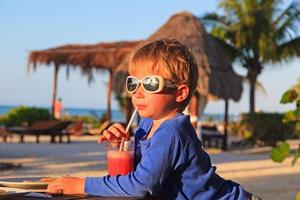 kleiner Junge, der Saft am tropischen Strand trinkt foto