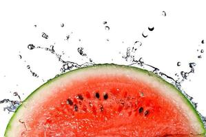 Scheibe Wassermelone spritzt ins Wasser foto