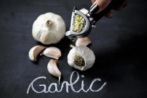 Knoblauchpresse mit dem Gemüse im Hintergrund foto