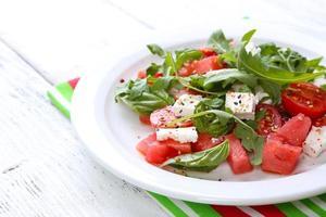 Salat mit Wassermelone, Tomaten, Feta, Rucola und Basilikumblättern foto