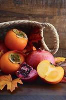 Korb mit frischen Kakis und Granatäpfeln foto