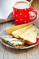 Frühstück: Blauschimmelkäse, Vollkornchips, Birne und Kaffee mit Milch foto