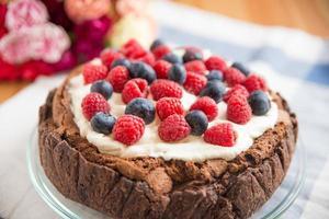 Schokoladenkuchen mit Sahne und gemischten Beeren foto