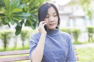 Frau, die auf dem Smartphone am Spielplatz spricht foto