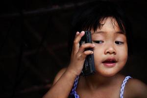 glückliches Baby, das auf Handy spricht