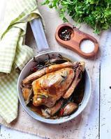 Gebratene Taube mit Cassouletbohnen, Zwiebeln, Speck, Karotten, Brokkoli, Rosmarin foto