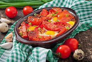 gebackene Tomaten mit Knoblauch und Eiern foto