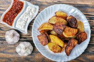 Kartoffelschnitze mit Sauce und Knoblauch foto