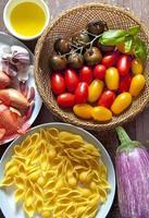 Zutaten für Nudelsalat. bunte Tomaten, Zwiebeln, Knoblauch, e foto