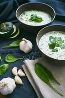 Suppe mit Spinat, Zucchini und Knoblauch auf einem Tisch foto