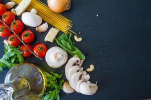 italienischer Hintergrund - Nudeln, Tomaten, Zwiebeln, Pilze, Olivenöl, Rucola foto