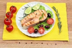 leckerer gegrillter Lachs mit Gemüse auf Holztisch foto