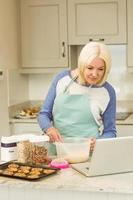 glückliche Blondine, die Teig nach Online-Rezept zubereitet foto