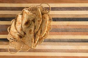 köstlich gebackene Naan-Fladenbrotscheiben im Korb auf Schneidebrett foto